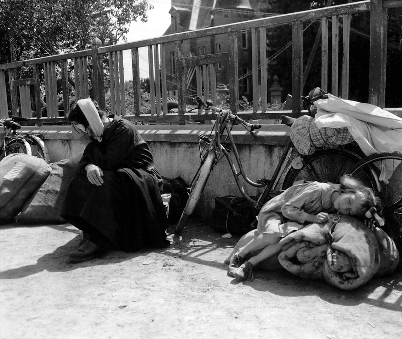 """Refugees fleeing the fighting have brought their bicycles and bundles into a school yard. 10th August 1944. A little girl is lying exhausted on a rolled blanket, while her grandmother is sitting next to her. Her white cap is a """"bachelique"""" knitted crochet. Many people from the fighting in Mortaine, just to the south have been seeking refuge in Saint-Pois during August 1944. Mortaine was the final battle for Nornandy. Saint-Pois, Normandy, France. (Photo by Galerie Bilderwelt/Getty Images)"""