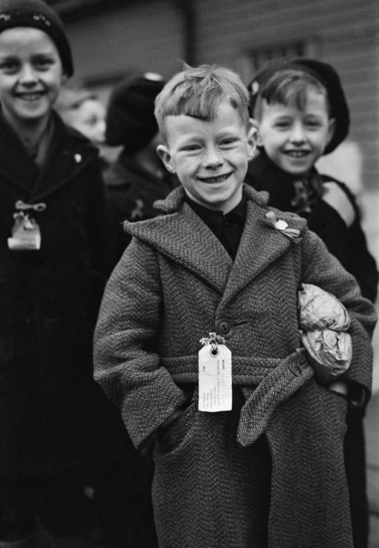 Dutch Child Refugees: Arrival In Britain At Tilbury, Essex, England, UK, 1945, A small Dutch boy smiles for the camera upon arrival at Tilbury in Essex. He is carrying a small paper parcel under his arm, which contains all his luggage. He, and the other children, (some of whom can be seen behind him) all have labels pinned to their coats which bear their names, home address and destination, 11 March 1945. (Photo by Ministry of Information Photo Division Photographer/ IWM via Getty Images)