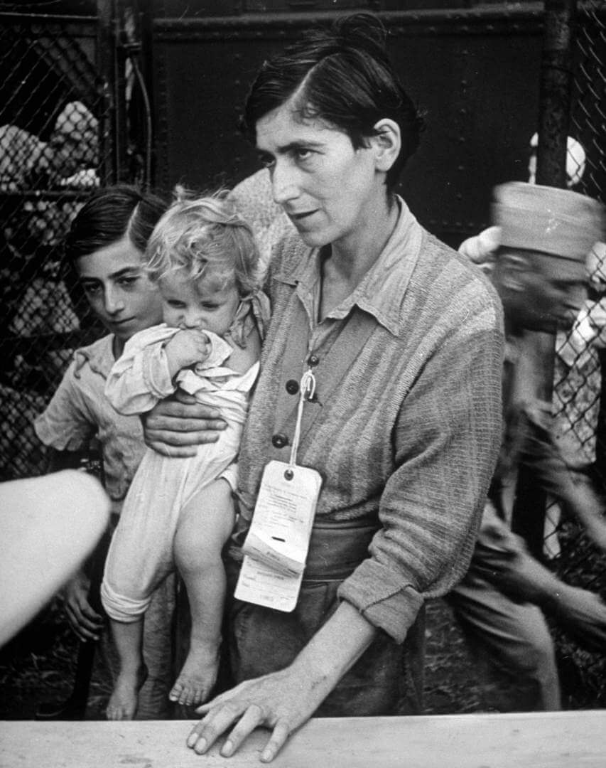 Swiss Jew Eva Bass, formerly a nightclub singer in Paris, entering refugee camp at Fort Ontario, with her children Yolanda and Joachim, whom she carried on a sixty-kilometer trek through the fighting lines to reach American transport ship Henry Gibbins.