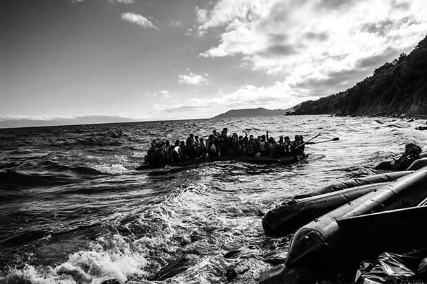 Migrants arrive on a dinghy after crossing from Turkey to Lesbos. Greece has been overwhelmed this year by record numbers of migrants. More than 250,000 people have reached Greece so far this year, the vast majority of them Syrians or Afghans fleeing conflict.
