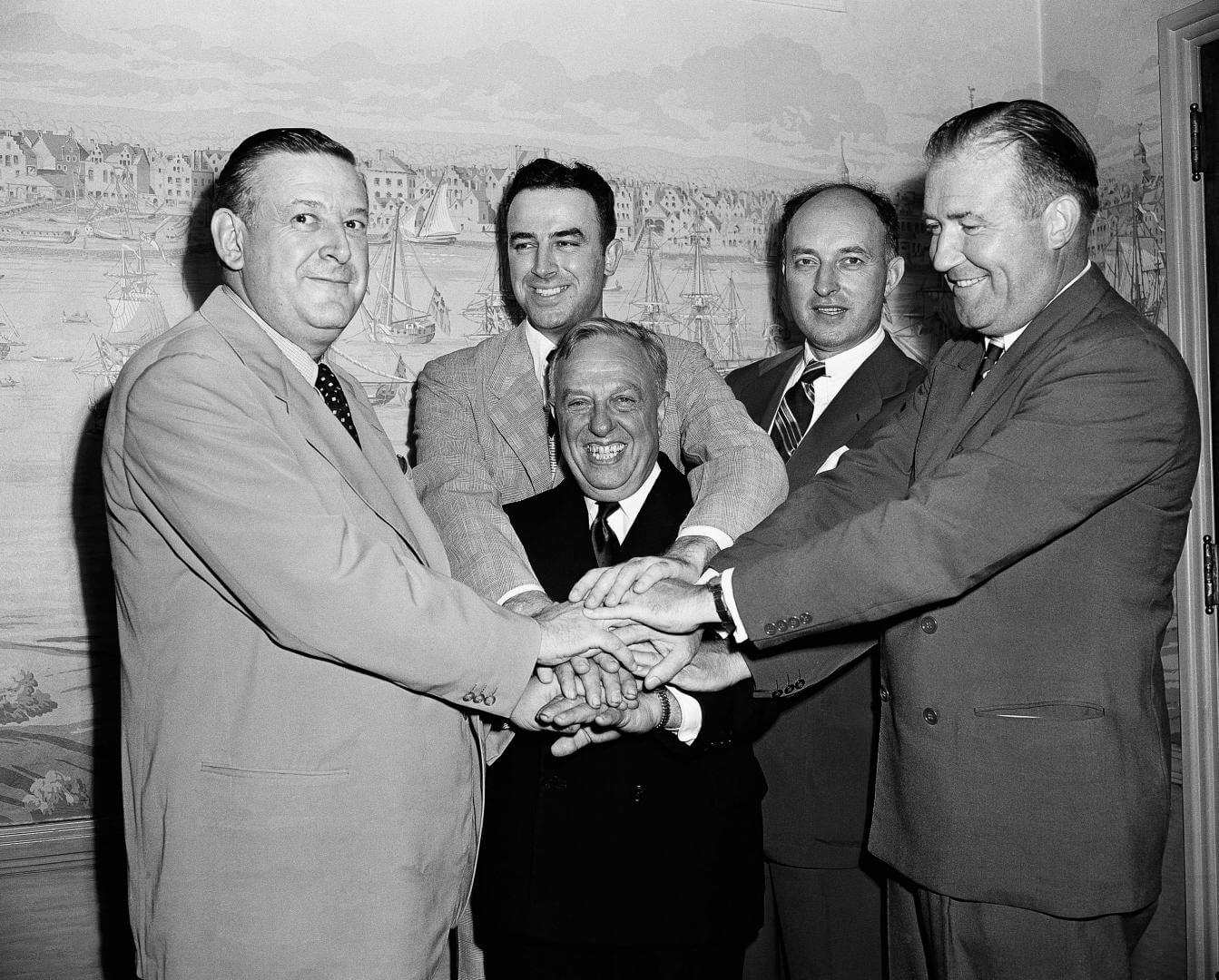 Representatives of the National Basketball League and Basketball Association of America, shake hands after agreeing to a merger of the two circuits into an 18-team organization to be known as the National Basketball Association, Aug 3, 1949, New York. Grouped around the smiling Maurice Podoloff, center, are left to right: Ike Duffey, Leo Ferris, Ned Irish, and Walter Brown. (AP Photo/John Lent)