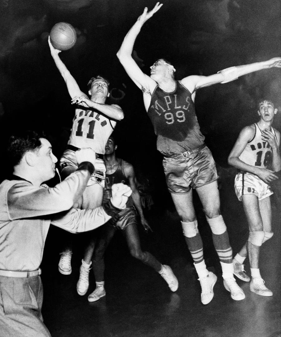 George Mikan (99), star Minneapolis Lakers center, breaks up a shot by Bob Davies, Rochester Royals guard (11) in the decisive game of the National Basketball Association's Western Division playoffs last night, April 4, 1951 in Rochester, N.Y. Rochester, won, 80-75. (AP Photo)