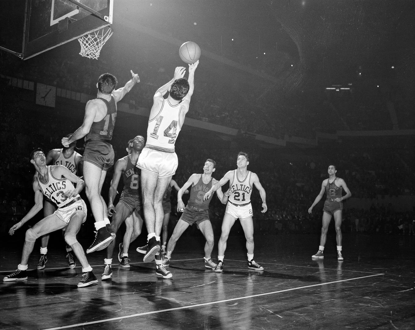 Bob Cousy (14) of the Boston Celtics takes a rebound off the backboard after an attempted basket by Dick McGuire (15) of the New York Knickerbockers in the fourth quarter of their NBA playoff game at the Boston Garden in Boston, Mass., March 26, 1953. Other identifiable players are: Bob Harris (13) and Bill Sharman (21) of the Celtics: Nat Clifton (8) and Ernie Vandeweghe (9) both of the Knicks. The Celtics won 86-70. (AP Photo/Bill Chaplis)