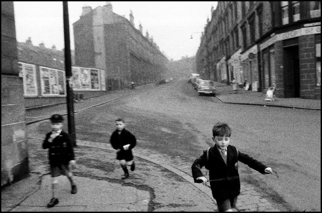 UK. 1960. Three boys running in streets.