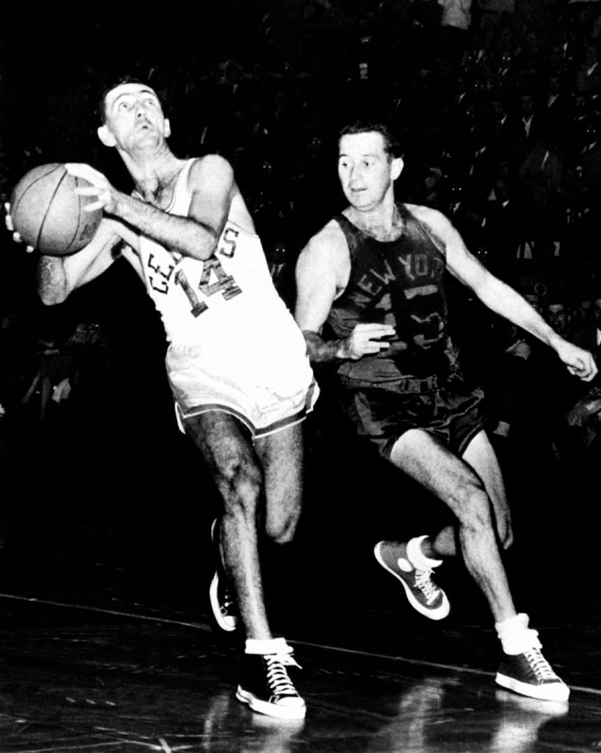 BOSTON, MA - 1950: Bob Cousy #14 of the Boston Celtics drives to the basket against Dick McGuire #15 of the New York Knicks at the Boston Garden circa 1950 in Boston, Massachusetts. NOTE TO USER: User expressly acknowledges that, by downloading and or using this photograph, User is consenting to the terms and conditions of the Getty Images License agreement. Mandatory Copyright Notice: Copyright 1950 NBAE (Photo by: NBA Photo Library/NBAE via Getty Images)